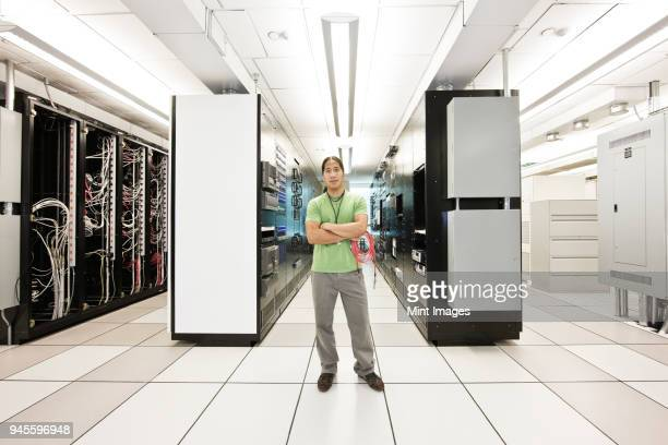 Portrait of an Asian American computer technician in a large computer server room