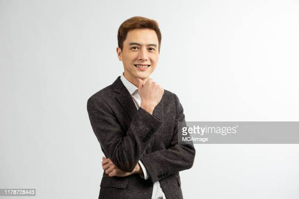a portrait of an asian businessman in a dark suit in a studio - 顎に手をやる ストックフォトと画像