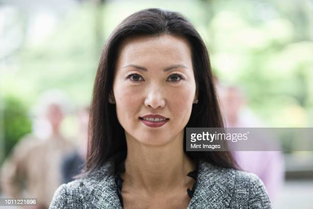 portrait of an asian businesswoman in the lobby of a convention centre. - korean ethnicity stock pictures, royalty-free photos & images