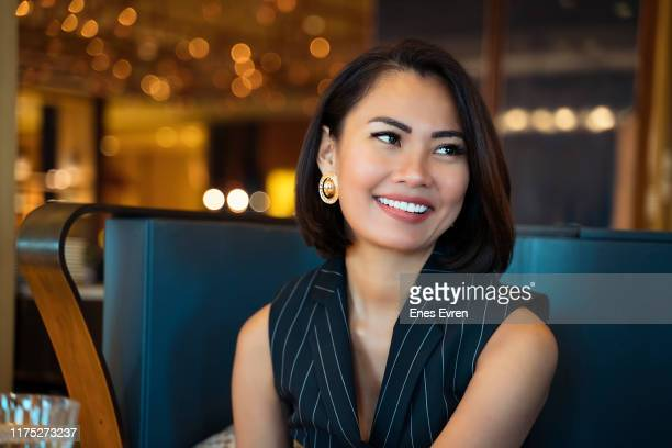 portrait of an asian businesswoman smiling at the camera in office - high society stock pictures, royalty-free photos & images