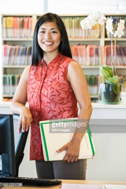 A portrait of an Asian businesswoman standing in her office with file folders in the background.