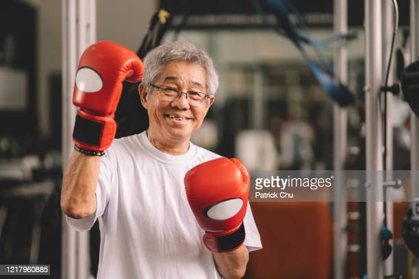 portrait of an asian chinese senior citizen boxer in gym - boxing stock pictures, royalty-free photos & images