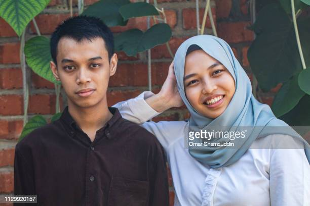 Portrait of an Asian couple with red brick background