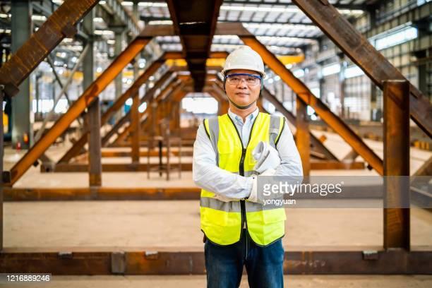retrato de um engenheiro asiático em uma fábrica de aço - plano americano - fotografias e filmes do acervo