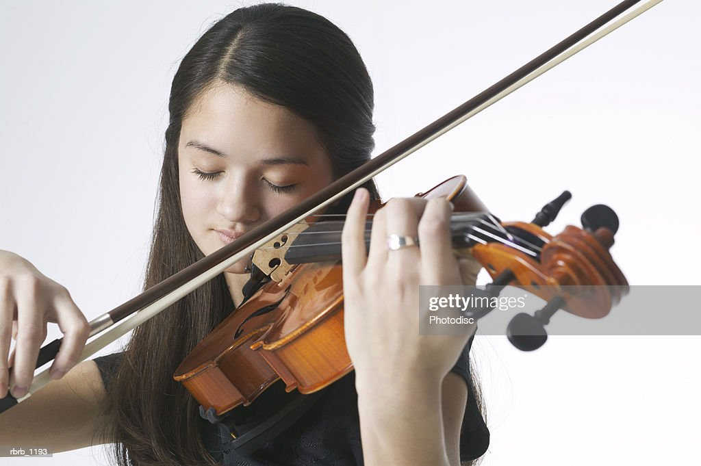 portrait of an asian female teen in a black dress as she plays her violin : Stockfoto