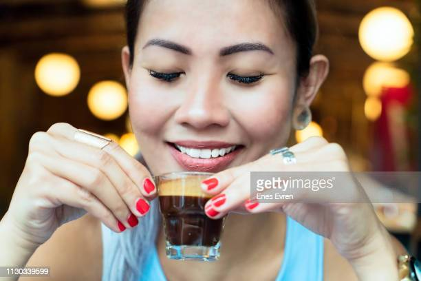 Portrait of an Asian woman drinking espresso coffee - close up