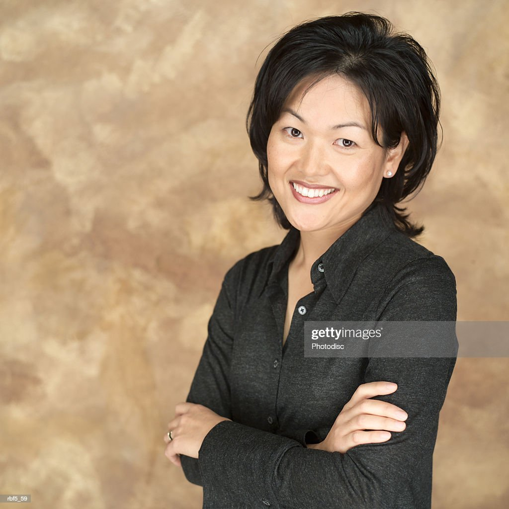 portrait of an asian woman in a black shirt as she folds her arms as she looks into the camera : Stockfoto