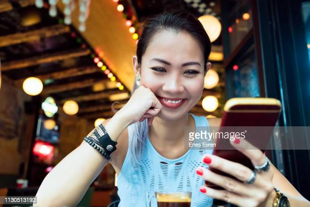 Portrait of an Asian woman using mobile phone in a luxurious restaurant