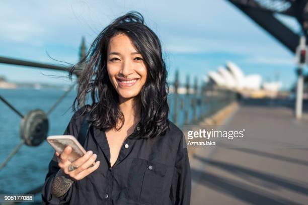 portrait of an asian woman using smart phone - sydney harbour bridge stock pictures, royalty-free photos & images