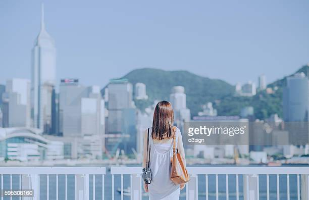 Portrait of an Asian woman with vintage medium format camera overlooking and enjoying the iconic view of Hong Kong skyline on a breezy sunny day