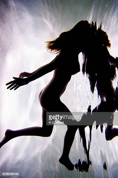 Portrait of an athletic nude female model swimming underwater in a swimming pool.