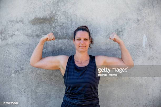 portrait of an athletic, strong woman in black singlet flexing her muscles - showus stock pictures, royalty-free photos & images
