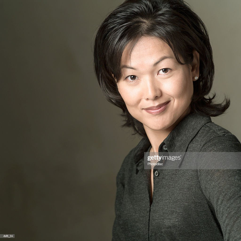 portrait of an attractive asian woman in a black shirt as she smiles into the camera : Stockfoto