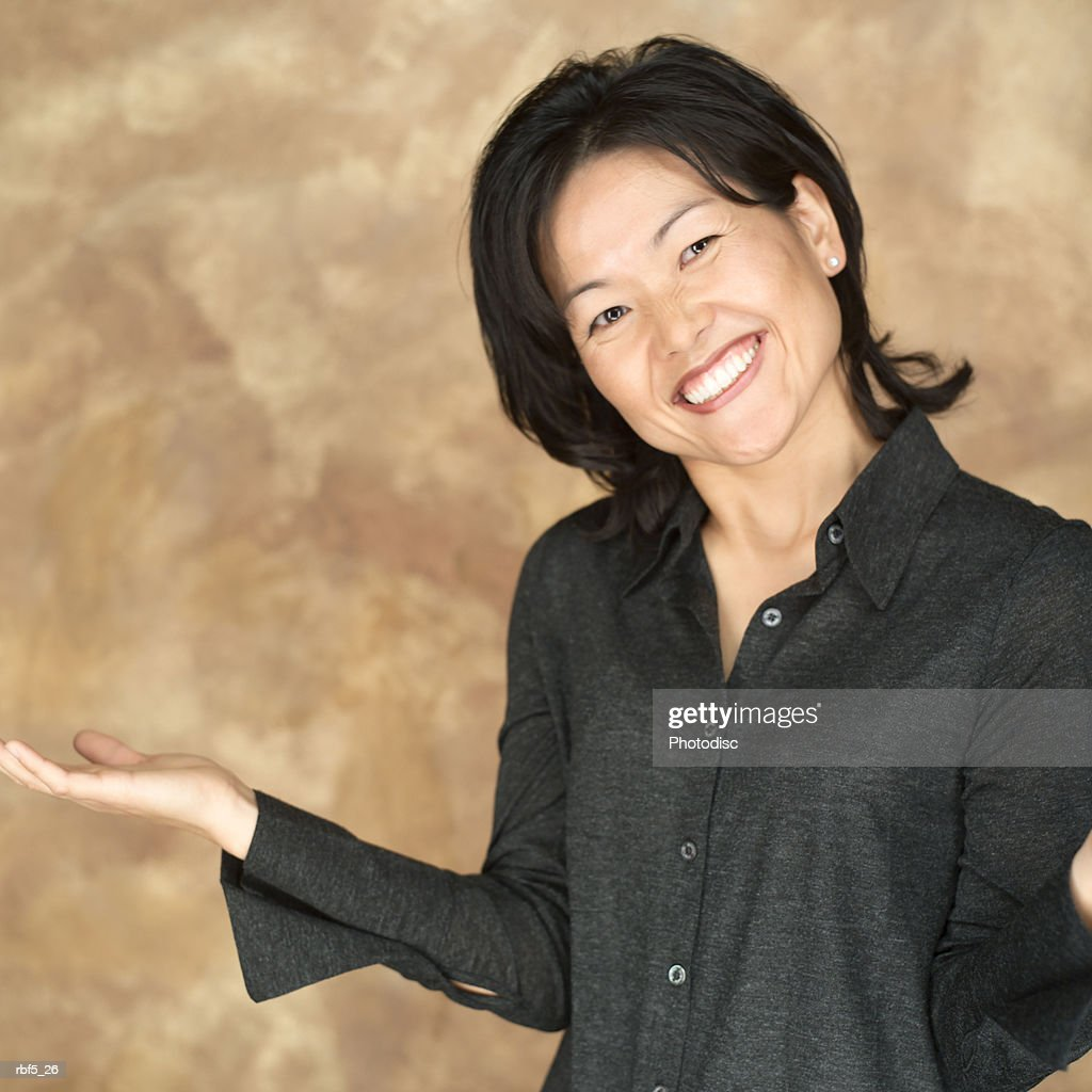 portrait of an attractive asian woman in a black shirt as she gestures with her arm and smiles : Stockfoto