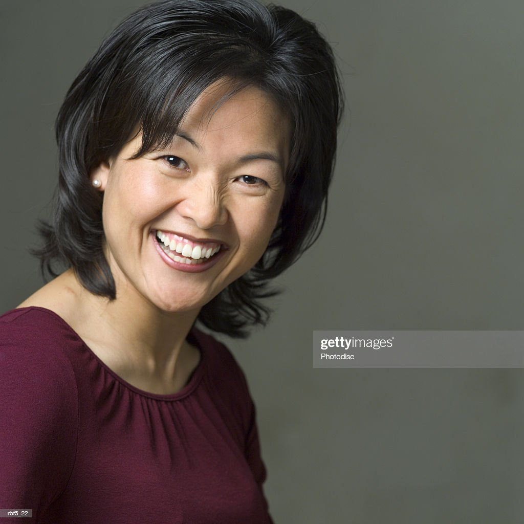 portrait of an attractive asian woman in a purple blouse as she smiles into the camera : Stockfoto