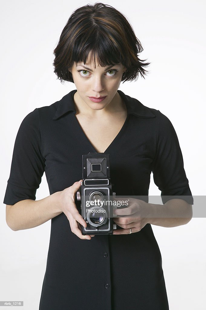 portrait of an attractive brunette woman in a black dress stands using an old camera : Stockfoto