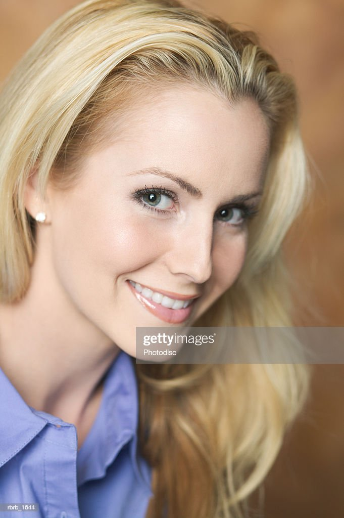portrait of an attractive caucasian blonde woman in a blue shirt as she turns and smiles : Stock Photo