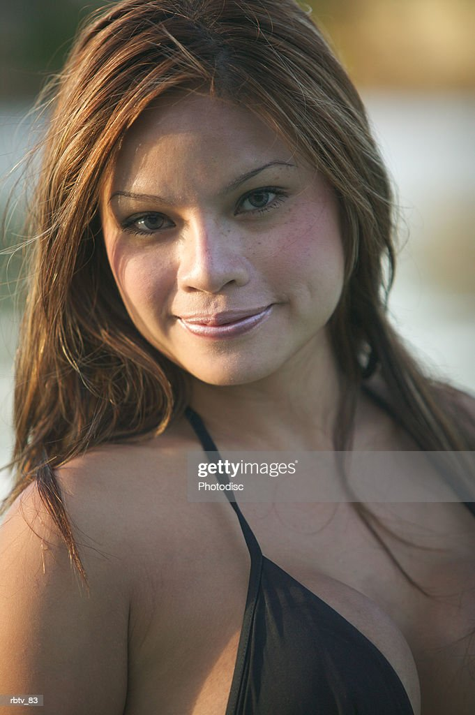 portrait of an attractive ethnic woman in a black swimsuit as she smiles slightly : Foto de stock