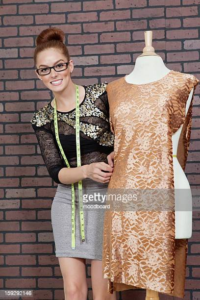portrait of an attractive female fashion designer adjusting cloth on tailor's dummy - デザイナー服 ストックフォトと画像