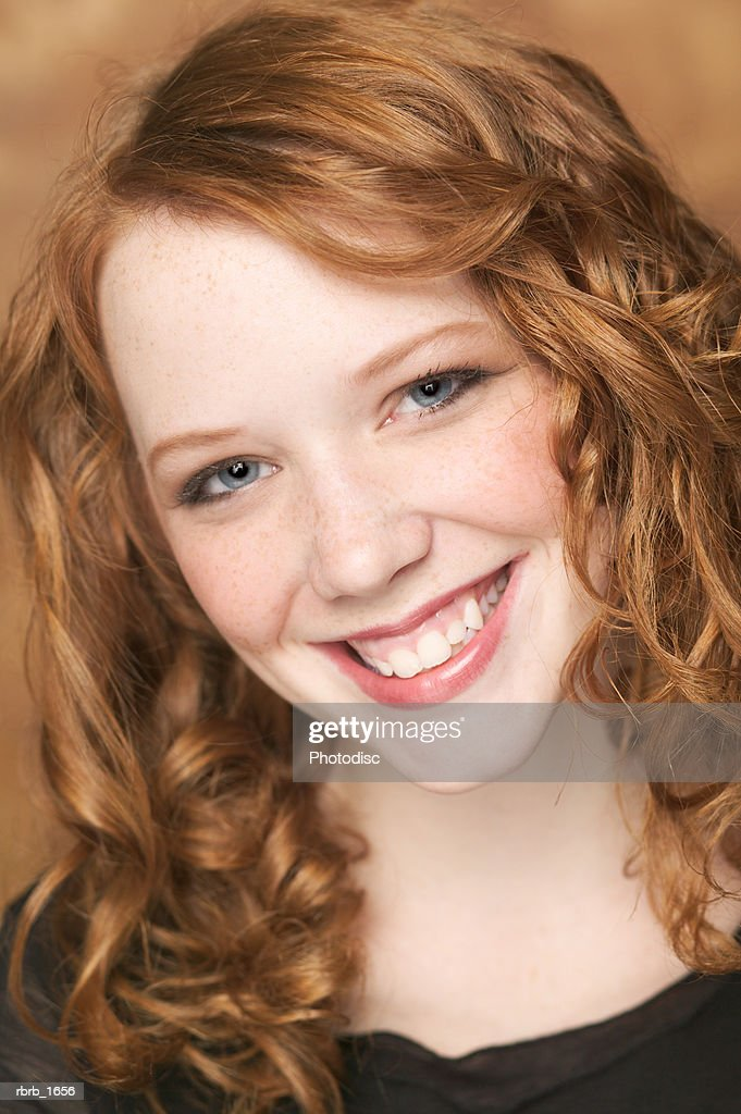 portrait of an attractive female redheaded teen in a black shirt as she smiles brighty : Stockfoto