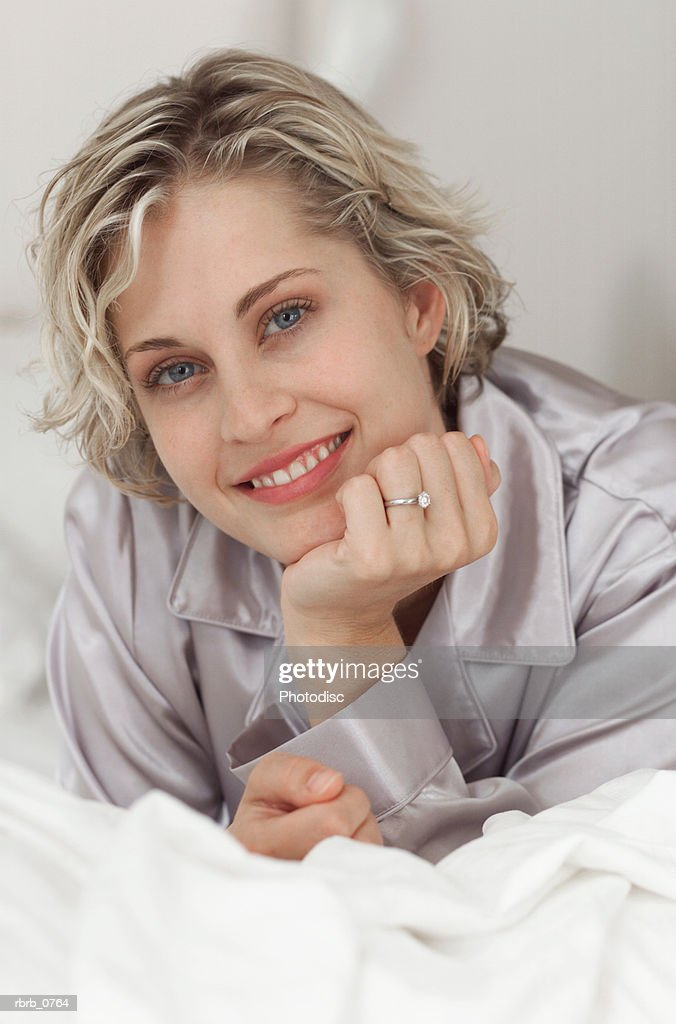 portrait of an attractive young blonde woman as she lays on her bed in her pajamas : Stockfoto