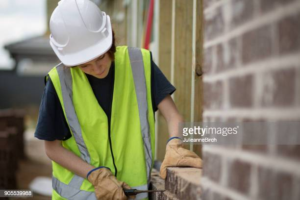 Portrait of an Australian woman bricklayer on building site building a wall