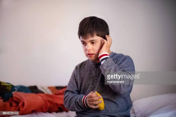 portret van een authentiek jongen van 12 jaar oud met autisme en het syndroom van down in dagelijks leven - 12 13 jaar stockfoto's en -beelden