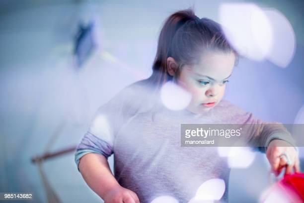 portrait of an authentic girl of 12 years old with autism and down syndrome in daily lives - autismo foto e immagini stock