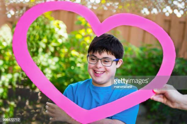 Portrait of an Autistic and down syndrome boy inside a heart shape