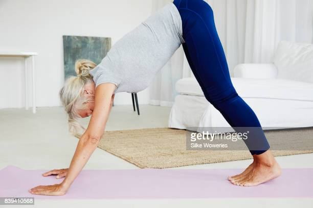 portrait of an content gray haired woman doing yoga at home