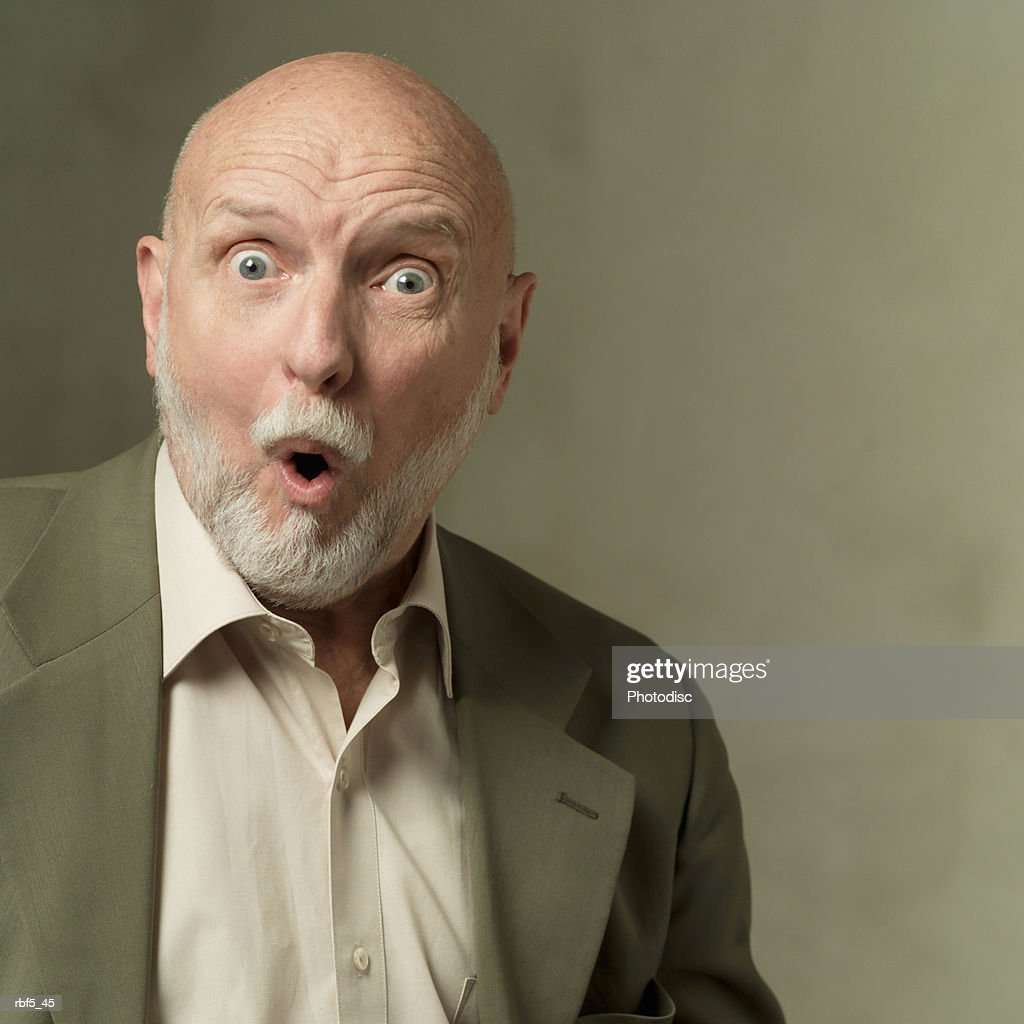 portrait of an elderly bearded caucasian man in a olive green suit as he looks shocked and surprised : Stock Photo