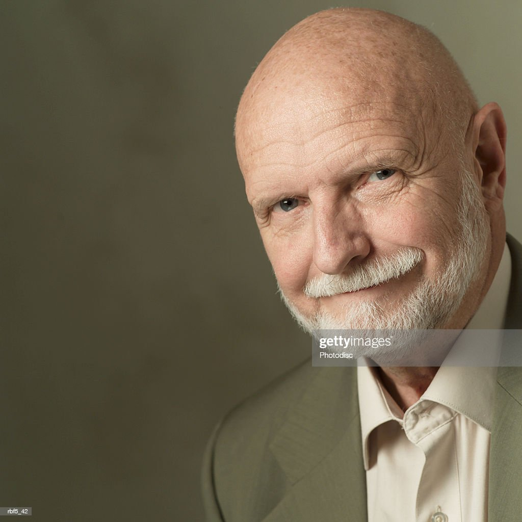 portrait of an elderly bearded caucasian man in a olive green suit smirks into the camera : Stockfoto