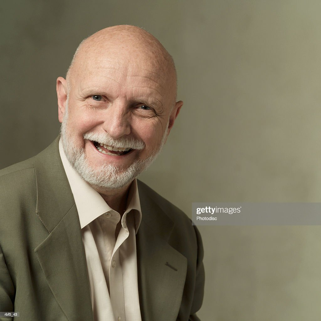 portrait of an elderly bearded caucasian man in a olive green suit smiles into the camera : Stockfoto