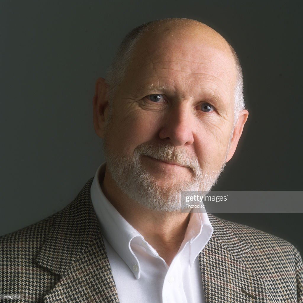 portrait of an elderly caucasian man with a beard as he smiles slightly : Stock Photo