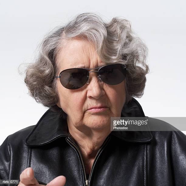 portrait of an elderly caucasian woman in a leather jacket and sunglasses as she points at the camera and scowls