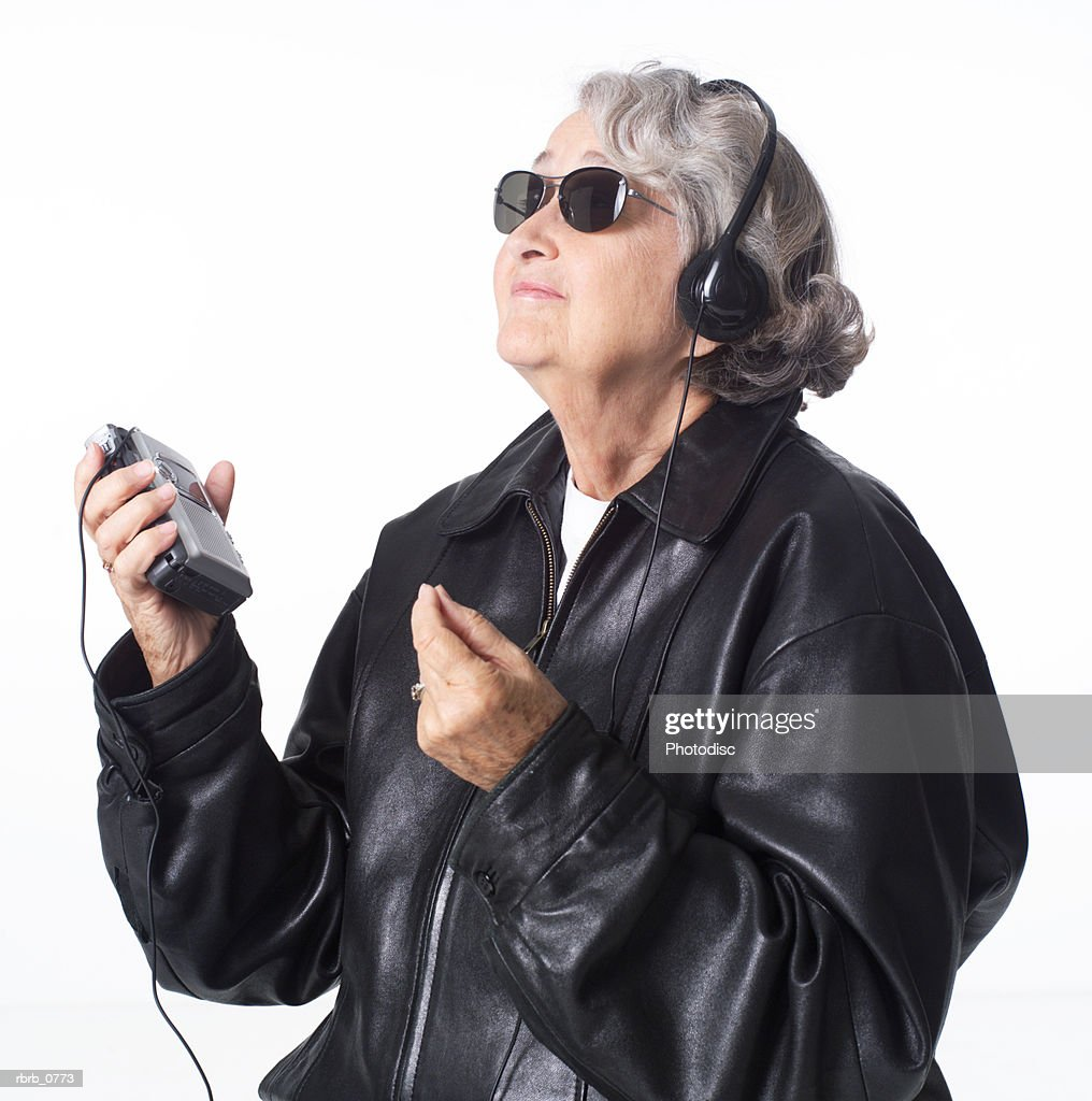 portrait of an elderly caucasian woman in a leather jacket and sunglasses as she listens to music through headphones : Stockfoto