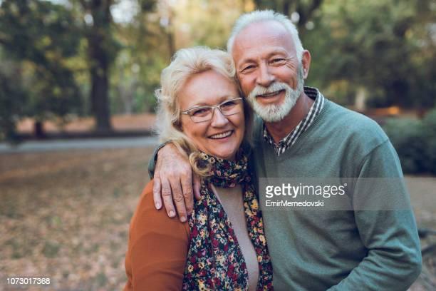 portrait of an elderly couple in the park - 65 69 anni foto e immagini stock
