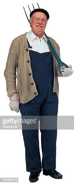 Portrait of an elderly man holding a pitch fork over his shoulder