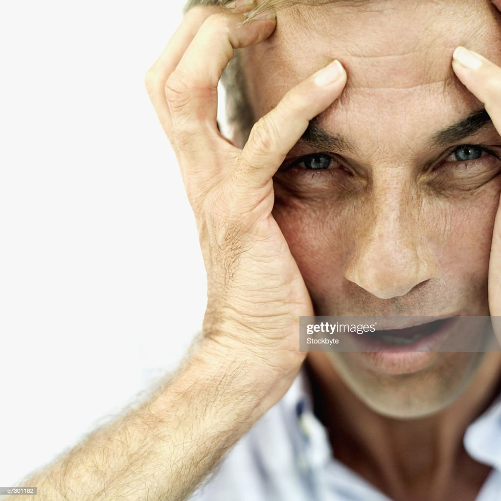 Portrait of an elderly man looking at camera touching his head : Stock Photo