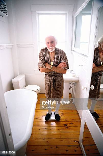 portrait of an elderly man standing on a weighing scale in the bathroom