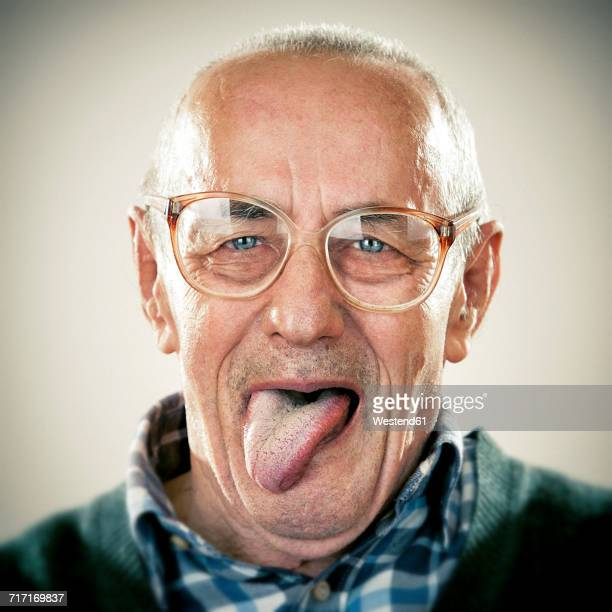 portrait of an elderly man, sticking his tongue out - lengua humana fotografías e imágenes de stock