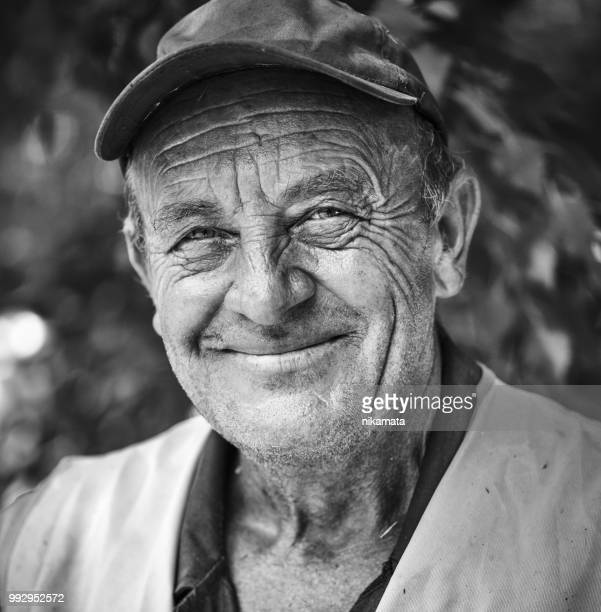 portrait of an elderly smiling man - black and white face stock photos and pictures