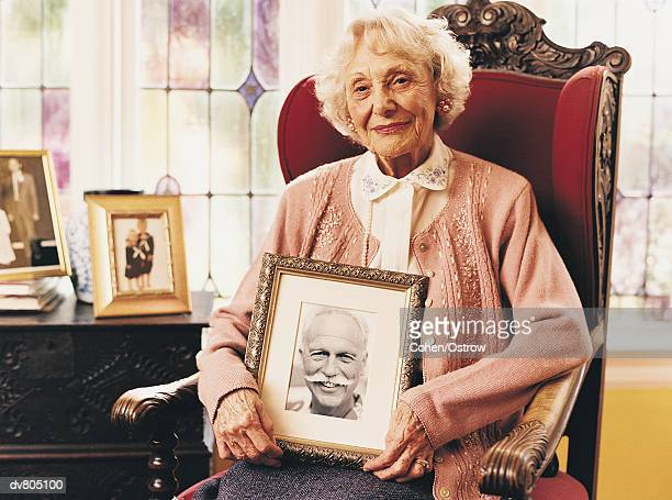 portrait of an elderly widow holding a photograph of her dead husband - dead female bodies stock pictures, royalty-free photos & images