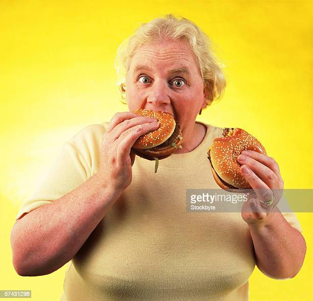 Portrait of an elderly woman eating two hamburgers