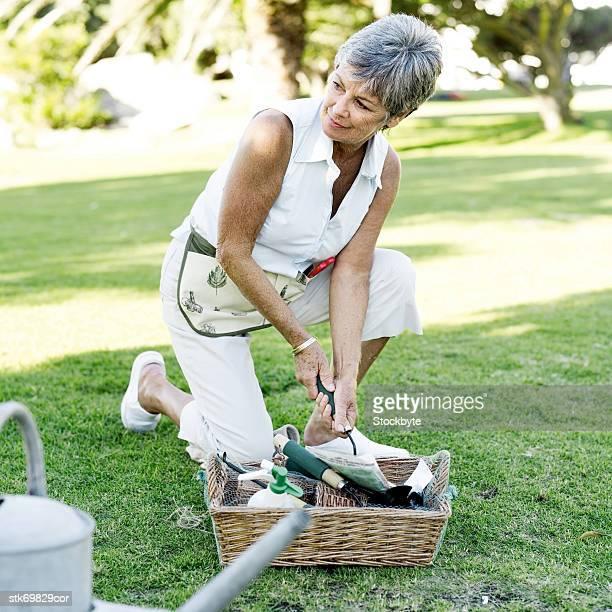 portrait of an elderly woman gardening in a yard