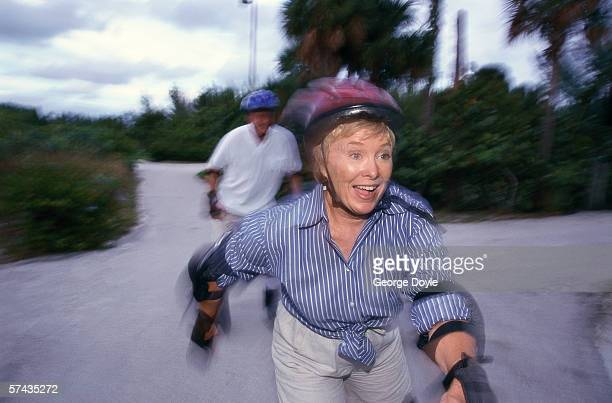 portrait of an elderly woman skating wearing protection gear