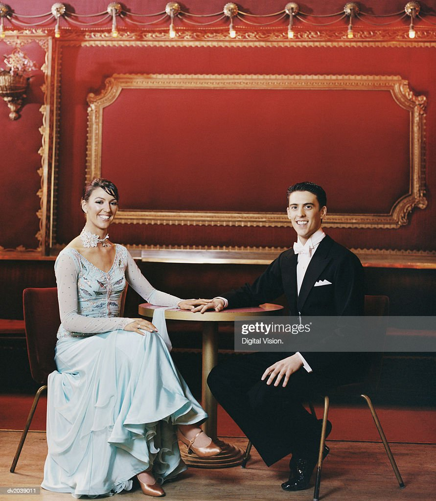Portrait of an Elegantly Dressed Couple Sitting at a Table : Stock Photo
