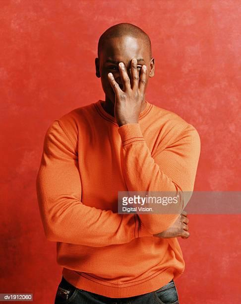 portrait of an embarrassed man, peeking from behind his hand - verdecktes gesicht stock-fotos und bilder