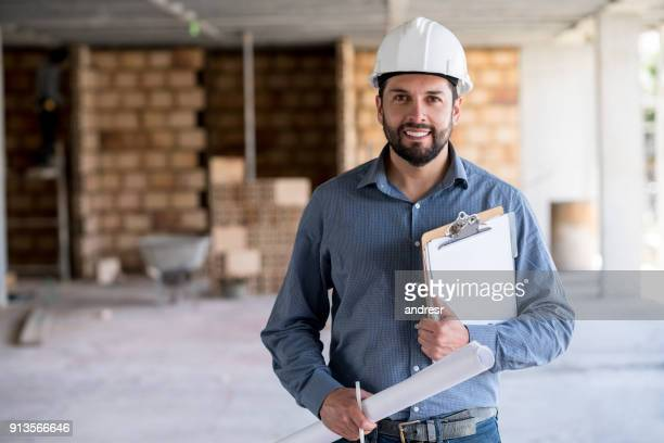 porträt eines ingenieurs hält eine blaupause auf einer baustelle - architekturberuf stock-fotos und bilder