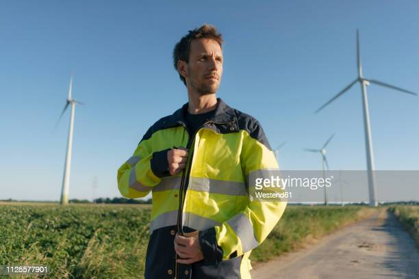 portrait of an engineer on field path at a wind farm - jacket stock pictures, royalty-free photos & images